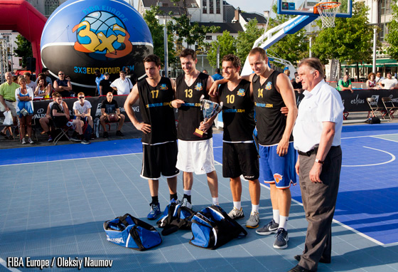 FIBA Europe acting president Cyriel Coomans presents the Elite Men Trophy to We Get Buckets of Belgium - the winners of elite men category here in Antwerp