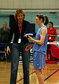 Year of Womens Basketball Project Manager Esther Wender presents Sally Naylor with her MVP award.