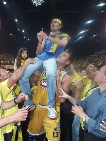 Radislav Curcic helps a fan cut down the net after Maccabi's SuproLeague final four win